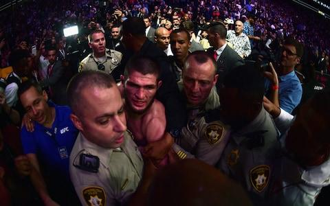 Khabib Nurmagomedov of Russia is escorted out of the arena - Credit: Harry How/Getty Images