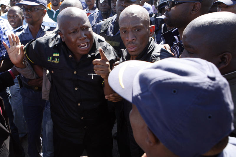 Firebrand politician Julius Malema, left, argues with police officers, at Lonmin Platinum Mine near Rustenburg, South Africa, Monday, Sept. 17, 2012. London-registered Lonmin PLC announced it is halting construction of a new shaft, putting 1,200 people out of work, as the bloody and bitter strike at its beleaguered South African platinum mine dragged on its fifth week. The strikes that have halted work at seven gold and platinum mines have spread to the chrome sector, according to the official South African Press Association. Meanwhile, police blocked rabblerousing politician Julius Malema from addressing some 3,000 strikers gathered at a stadium at the Lonmin mine at Marikana, northwest of Johannesburg. (AP Photo/Themba Hadebe)