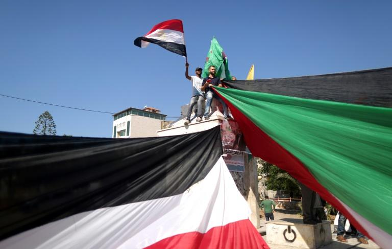 Gazans wave the flags of Egypt and Palestine as they celebrate a unity agreement reached in Cairo between rival Palestinian factions Hamas and Fatah on October 12, 2017