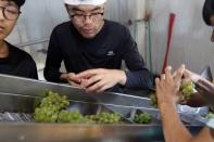 Staffs prepare fresh harvest grapes into the processer to make wine at Shu Sheng Leisure Domaine in Taichung