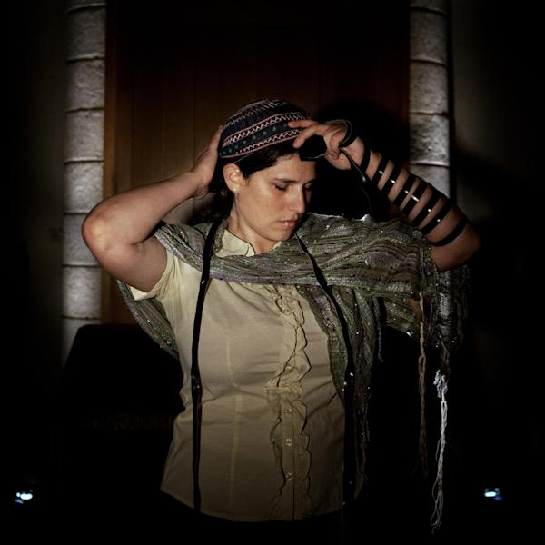 In this photo taken Wednesday, June 19, 2013, Israeli Rabbi of the Ramot Zion community, Chaya Baker poses for a photo as she puts on Tefilin also known as Phylacteries at a Synagogue in Jerusalem. Depending on whom you ask, these women are either pioneers or provocateurs. They are part of the liberal Reform or Conservative streams of Judaism which allow women to perform rituals typically reserved for men under Orthodox Judaism, the dominant form of Judaism in Israel. (AP Photo/Sebastian Scheiner)
