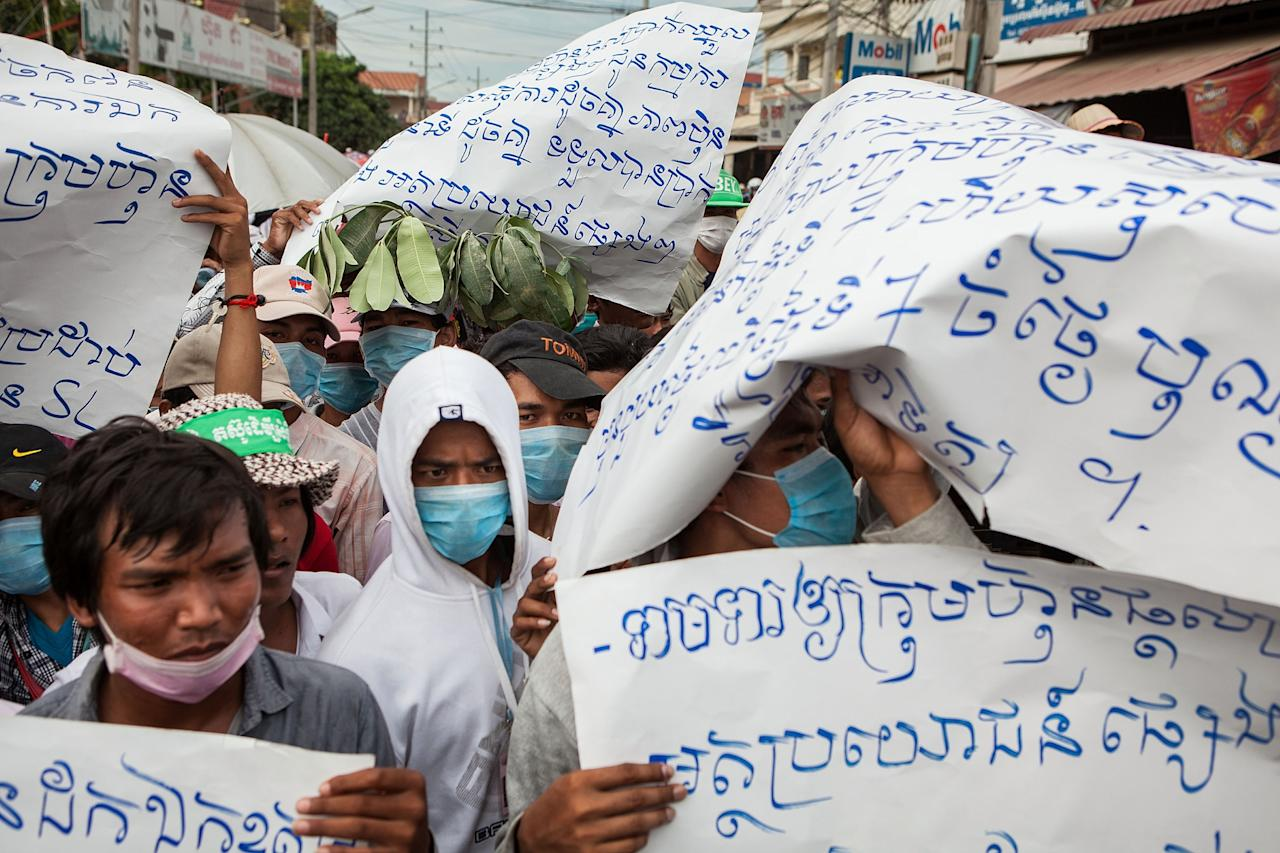 PHNOM PENH, CAMBODIA - AUGUST 27: Garment factory workers from SL Garment stand at a police blockade as they marched from the factory in Phnom Penh's Meanchy district to the Ministry of Social Affairs to demanding an increase in wages on August 27, 2013 in Phnom Penh, Cambodia. After negotiations failed with factory management, workers of SL Garment who supplies brands like Gap, Levi's and H&M marched to the Ministry of Social Affairs in central Phnom Penh. (Photo by Nicolas Axelrod/Getty Images)