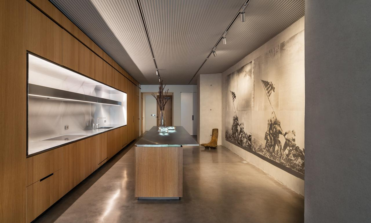 The large-scale kitchen of the three-bedroom model is ideal for entertaining, and custom ridges in the concrete throughout the lofts make for flexible lighting options. Here, a mural by the Bruce High Quality Foundation graces one wall.