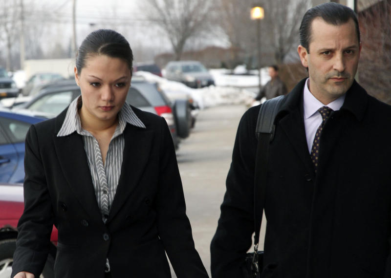 Dawn Nguyen, left, arrives with one of her lawyers at Henrietta Town Court Tuesday, Jan 8, 2013, in Rochester, N.Y. Nugyen is accused of lying on a form when she bought guns later used by ex-convict William Spengler Jr. to kill two firefighters and wound three others in Webster, N.Y. (AP Photo/ Guy Solimano)