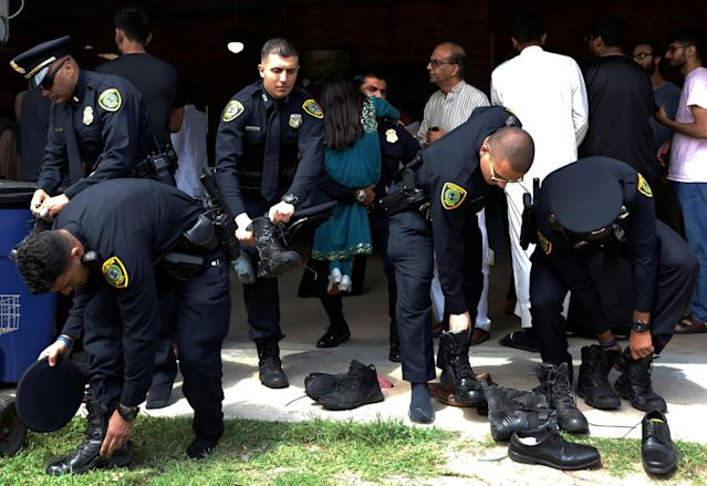 <p>Houston police officers put their shoes back on following a funeral prayer service for Sabika Sheikh at the Brand Lane Islamic Center in Stafford, Texas, May 20, 2018. (Photo: Jonathan Bachman/Reuters) </p>