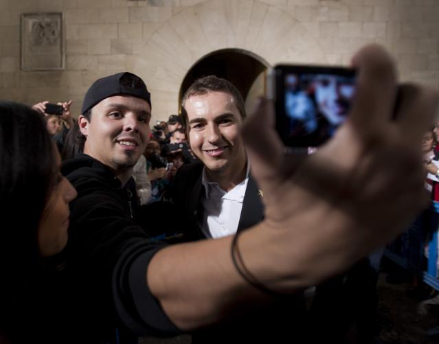 Moto GP world champion Spain's Jorge Lorenzo (R) poses with a fan in Palma de Mallorca during a parade on November 19, 2012. AFP PHOTO/ JAIME REINAJAIME REINA/AFP/Getty Images