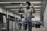 Yuki Kitazumi, a Japanese freelance journalist detained by security forces in Myanmar in mid-April and accused of spreading fake news criticizing the military coup, gestures to speak to the media as he arrives at Narita International Airport, in Narita, east of Tokyo. (AP Photo/Eugene Hoshiko)
