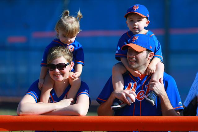 <p>Young fans of the New York Mets, perched on the shoulder of their parents, watch players work out during spring training in Port St. Lucie, Fla., Feb. 23, 2018. (Photo: Gordon Donovan/Yahoo News) </p>