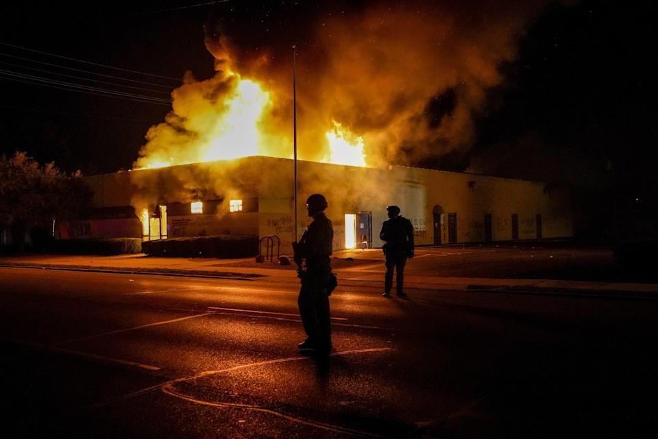 Police stand near a Department of Corrections building set ablaze during protests in Kenosha, Wis.