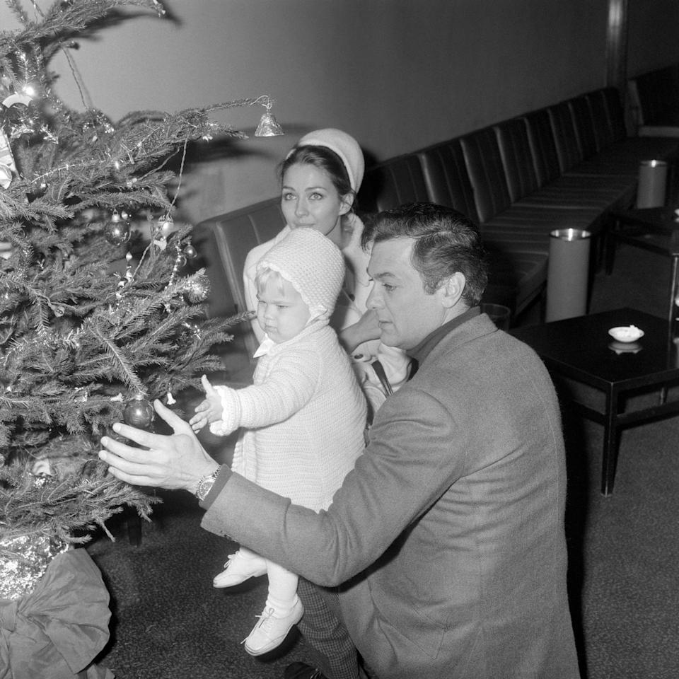 <p>The <em>Some Like it Hot</em> actor, along with his wife Christine Kaufmann and their daughter Alexandra, admire a Christmas tree at the London Airport in 1965.</p>