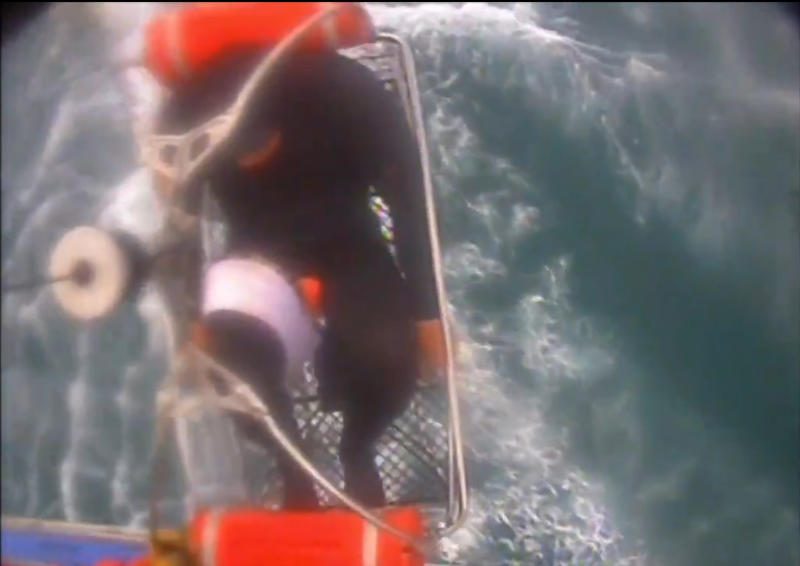 """In this Saturday, Dec. 21, 2019, image taken from video released by the U.S. Coast Guard, a man, wearing a full-body wetsuit, is hoisted up from a boat into a helicopter near Santa Rosa Island, one of the Channel Islands in Southern California. A shark reportedly bit the surfer Saturday afternoon in a """"truly terrifying situation,"""" the Coast Guard said. The 37-year-old man had been surfing near Santa Rosa Island, one of the Channel Islands, during the attack, according to a news release. (U.S. Coast Guard Los Angeles via AP)"""