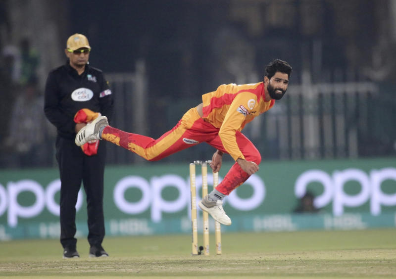 Islamabad United pacer Amad Butt, front, bowls while umpire Shozab Raza watches during their Pakistan Super League T20 cricket match at Gaddafi stadium in Lahore, Pakistan, Saturday, Feb. 22, 2020. (AP Photo/K.M. Chaudary)