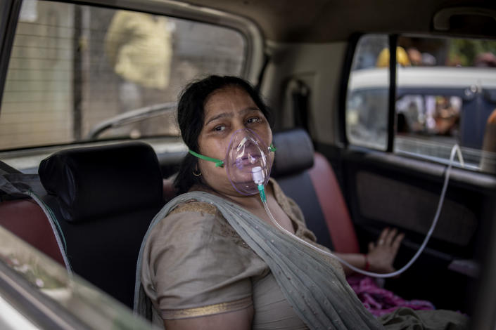 A COVID-19 patient sits inside a car and breathes with the help of oxygen provided by a Gurdwara, a Sikh house of worship, in New Delhi, India, Saturday, April 24, 2021. India's medical oxygen shortage has become so dire that this gurdwara began offering free breathing sessions with shared tanks to COVID-19 patients waiting for a hospital bed. They arrive in their cars, on foot or in three-wheeled taxis, desperate for a mask and tube attached to the precious oxygen tanks outside the gurdwara in a neighborhood outside New Delhi. (AP Photo/Altaf Qadri)