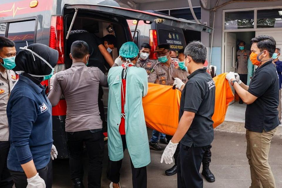 Disaster Victims Identification (DVI) police officers load a body bag onto a van in the aftermath of a prison fire at a hospital in Tangerang, Banten, Indonesia, 8 September 2021 (EPA)