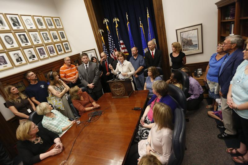 Surrounded by plaintiffs, Attorney General Lori Swanson, at podium, announces the legal settlement with Accretive Health Inc. Monday, July 30, 2012 in St. Paul, Minn. The settlement will bar Chicago-based Accretive Health Inc. from doing business in Minnesota for six years after she accused the medical revenue company of intrusive efforts to collect money from patients in several hospitals. Larson's husband was suffering from chest pains when an Accretive representative demanded payment before treatment. (AP Photo/The Star Tribune, Richard Tsong-Taatarii)  MANDATORY CREDIT; ST. PAUL PIONEER PRESS OUT; MAGS OUT; TWIN CITIES TV OUT