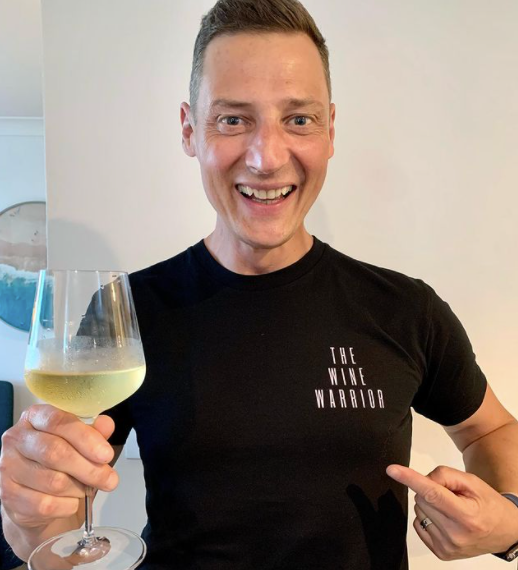 Merrick Watts holds glass of white wine SAS Australia tactic