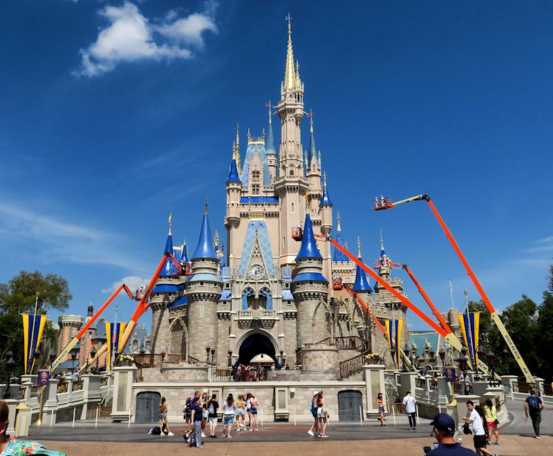 Workers at Walt Disney World paint Cinderella Castle in the Magic Kingdom, in Lake Buena Vista, Fla., on March 12, 2020. (Joe Burbank/Orlando Sentinel/Tribune News Service via Getty Images)