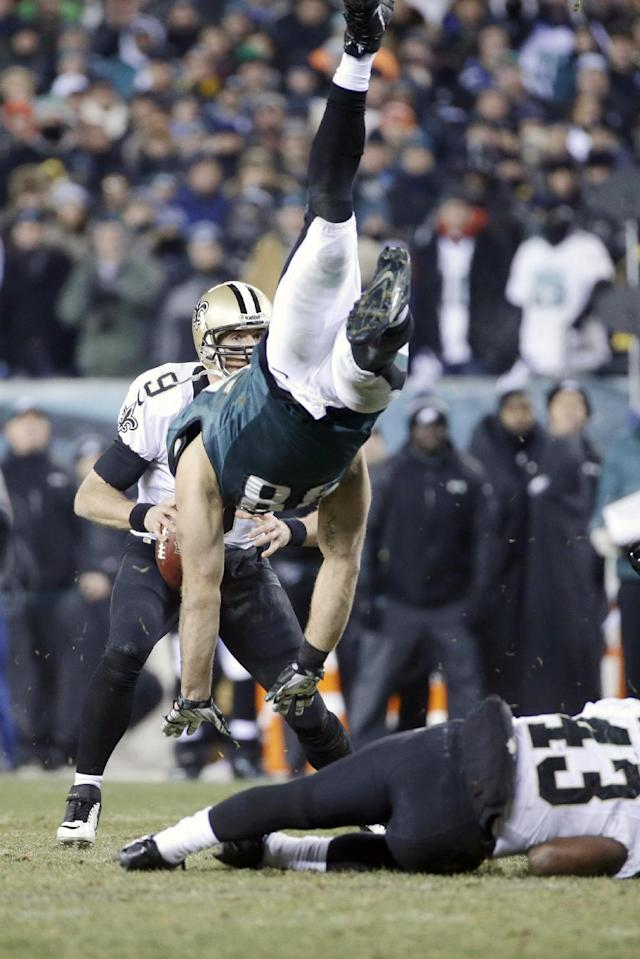New Orleans Saints' Drew Brees, left, tries to pass as Philadelphia Eagles' Connor Barwin, center, is upended by Darren Sproles during the second half of an NFL wild-card playoff football game, Saturday, Jan. 4, 2014, in Philadelphia. (AP Photo/Matt Rourke)