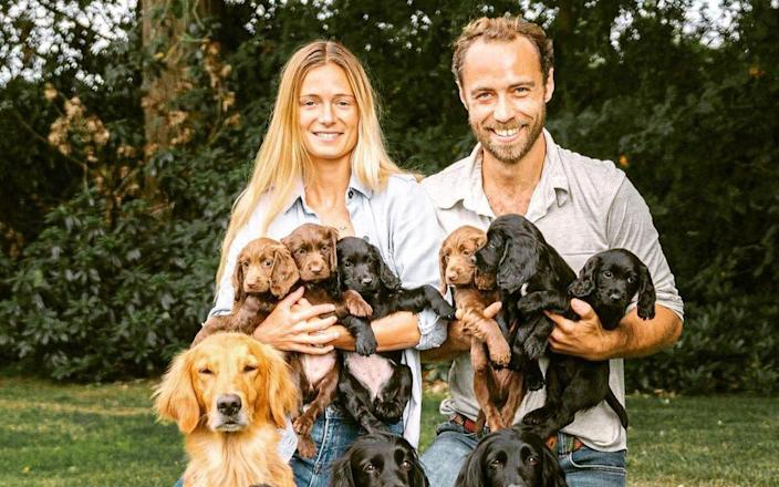 James Middleton and his fiancee Alizee Thevenet with the puppies, one of whom was given to the Cambridges last year