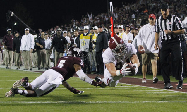 Alabama tight end Brian Vogler (84) dives into the end zone past Mississippi State defensive back Jamerson Love (5) for an 18-yard touchdown reception during the second quarter of an NCAA college football game, Saturday, Nov. 16, 2013, in Starkville, Miss. (AP Photo/Butch Dill)