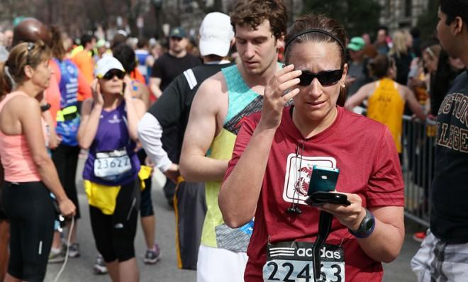 Runners check their phones after two bombs explode during the 117th Boston Marathon on April 15.