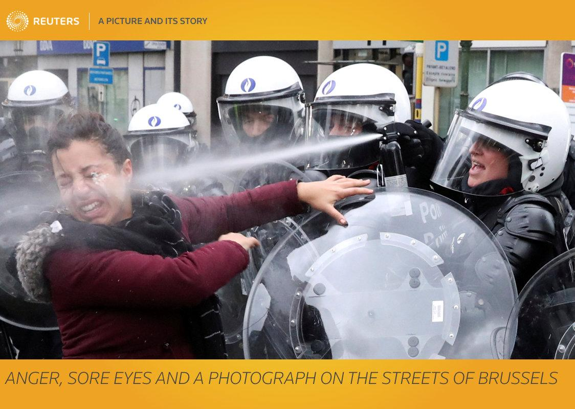 """Reuters photographer Yves Herman: """"Usually, a golden rule for a news photographer covering a scene of angry confrontation is to get close, but not involved. Sometimes, though, it's hard to avoid. """"Yellow vest"""" protests have in recent days spread to Belgium from France. I followed hundreds of people marching through Brussels on Saturday to demand lower fuel prices and better living conditions. They were blocked from reaching the government quarter by riot police using water cannon and tear gas. Some of the crowd hurled rocks and firecrackers at them. Police squads started surrounding protesters, sending in snatch teams to arrest individuals. As the march was organised on social media without approval from the authorities, police took the view that anyone involved could be detained and taken away. Most are quickly released without charge. When one young man was seized, a young woman with him rushed towards the line of police, shouting that he had done nothing wrong. She had no mask or helmet and nothing in her hands. She wasn't even wearing one of the fluorescent yellow vests adopted by the movement. As she yelled at a policewoman, another officer standing behind the front rank pointed and fired a pepper-spray gun, dousing the young woman in the face. The photo I took dramatically captured the white liquid's moment of impact and her anguished expression. She turned away crying and sat down on the road, her eyes and face inflamed. I had a bottle of eyewash as part of my own safety equipment. I put my camera down, asked her to look up and carefully dropped the soothing liquid into her eyes."""" REUTERS/Yves Herman/File photo     SEARCH """"TEARGAS HERMAN"""" FOR THIS STORY. SEARCH """"WIDER IMAGE"""" FOR ALL STORIES. TPX IMAGES OF THE DAY. Matching text: BELGIUM-PROTESTS/IMAGE"""