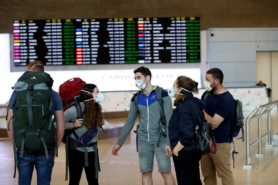Travelers wearing masks chat in the arrivals terminal after Israel said it will require anyone arriving from overseas to self-quarantine for 14 days as a precaution against the spread of coronavirus, at Ben Gurion International airport in Lod, near Tel Aviv, Israel March 10, 2020. REUTERS/Ronen Zvulun