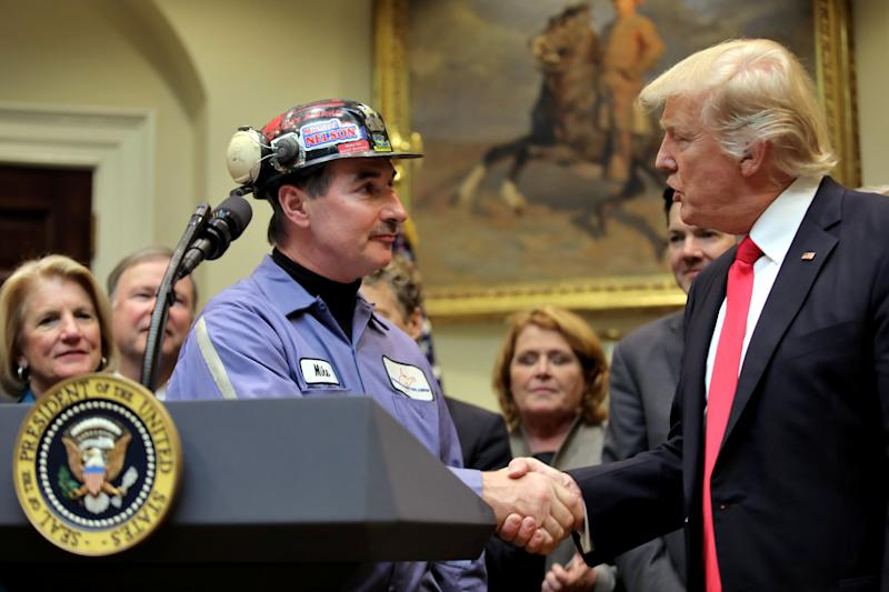 """Coal miner Michael Nelson shakes hands with President Donald Trump as Trump prepares to sign Resolution 38, which nullifies the coal industry's """"stream protection rule."""" (Carlos Barria / Reuters)"""