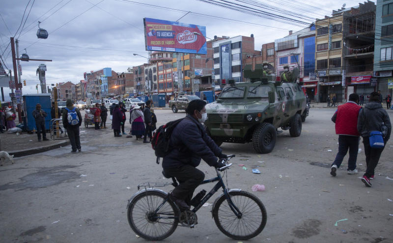 A man wearing a protective face mask against the spread of the new coronavirus, rides his bicycle past a military armored vehicle patrolling streets during a quarantine in El Alto, Bolivia, Friday, March 20, 2020. Authorities have decreed a quarantine from 5pm to 5am in an attempt to stop the spread of the new coronavirus. The vast majority of people recover from the COVID-19 disease. (AP Photo/Juan Karita)