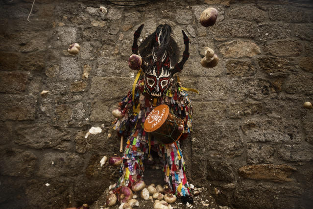 <p>People throw turnips at the Jarramplas as he makes his way through the streets beating his drum during the Jarramplas Festival in Piornal, Spain, Jan. 20, 2015. (Photo: Daniel Ochoa de Olza/AP) </p>