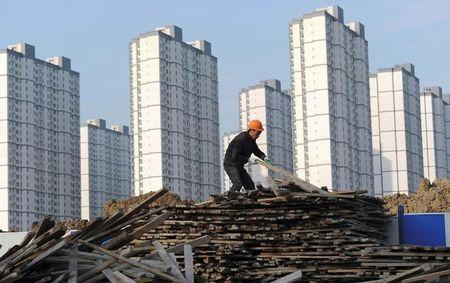 A labourer selects wooden planks as he works at a residential construction site in Hefei, Anhui province, China February 18, 2012.   REUTERS/Stringer/File Photo