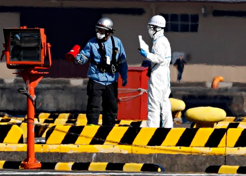 Officers in protective gears are pictured at a maritime police's base where people who were transferred from cruise ship Diamond Princess arrived in Yokohama,