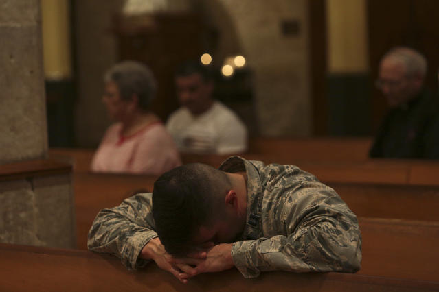 <p>Air Force Captain Emmanuel Rivera prays during the opening Mass of the Presbyteral Convocation at San Fernando Cathedral in San Antonio, Texas on Monday, Nov. 6, 2017. Special prayers were said and a display of candles memorialized the victims of the mass shooting at First Baptist Church in Sutherland Springs during the mass. (Photo: San Antonio Express-News via ZUMA Wire) </p>