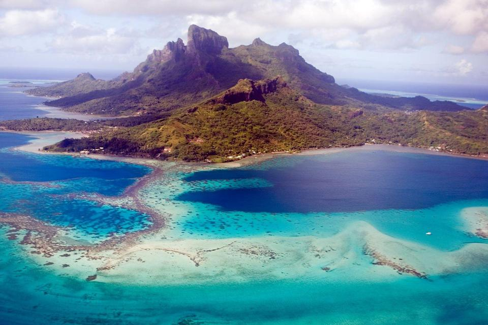 "<p>An ariel view of <a href=""https://www.tripadvisor.com/Tourism-g311415-Bora_Bora_Society_Islands-Vacations.html"" rel=""nofollow noopener"" target=""_blank"" data-ylk=""slk:this small South Pacific island"" class=""link rapid-noclick-resp"">this small South Pacific island</a> shows off its crystal clear blue lagoon protected by a massive coral reef. </p>"