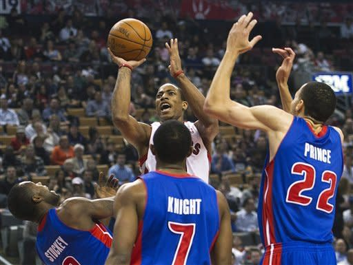Toronto Raptors forward DeMar DeRozan, top center, takes a shot past Detroit Pistons guard Rodney Stuckey, left, guard Brandon Knight, bottom center, and forward Tayshaun Prince, right, during first--half NBA basketball game action in Toronto, Wednesday, Feb. 22, 2012. (AP Photo/The Canadian Press, Nathan Denette)