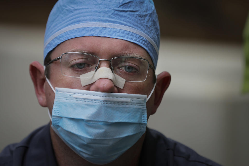 """Chaplain Will Runyon holds back tears as he speaks of the hardships and death amid the COVID-19 coronavirus outbreak outside of Phoebe Putney Memorial Hospital in Albany, Ga., on Monday, April 20, 2020. """"There's so much death right now, it piles up on you, it feels heavy,"""" Runyon said. He can feel it in his back, in his feet, like he's dragging something invisible behind him. """"It's happening so often, over and over, everyday."""" (AP Photo/Brynn Anderson)"""