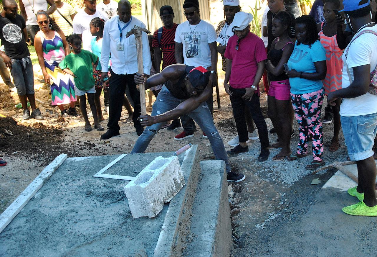 Jamaica's Olympic champion Usain Bolt (C) digs the grave for high jump star Germaine Mason, who died on April 20 in a motorbike crash on the outskirts of Kingston, in Grange Hill, Portland, Jamaica May 13, 2017. Picture taken May 13, 2017. REUTERS/Everard Owen