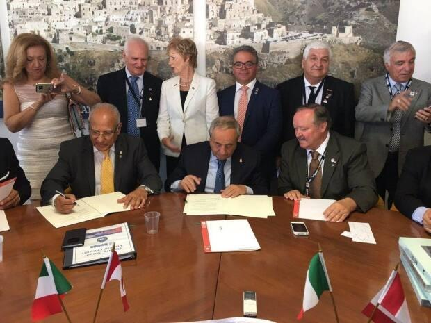 Former Toronto city councillor Vincent Crisanti, front left, signs a memorandum of understanding with Matera official during a 2017 trip to Italy. Liberal MPs Judy Sgro, back middle, and Francesco Sorbara, third from right beside Sgro, stand behind the signing ceremony. (Franceso Sorbara/Twitter - image credit)