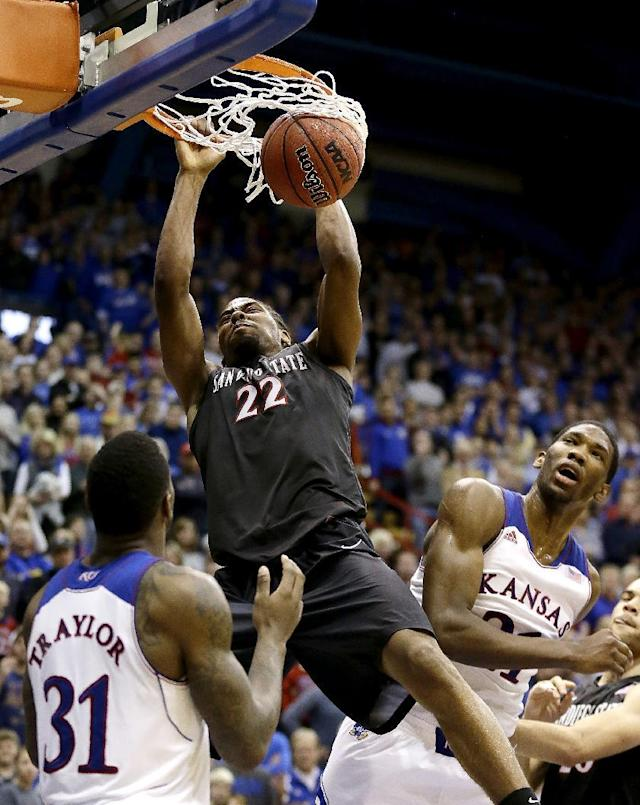 San Diego State's Josh Davis (22) gets between Kansas' Jamari Traylor (31) and Joel Embiid (21) to dunk the ball during the second half of an NCAA college basketball game Sunday, Jan. 5, 2014, in Lawrence, Kan. San Diego State won 61-57.(AP Photo/Charlie Riedel)