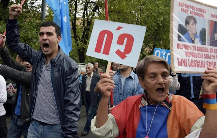 """An opposition protester holds a sign reading """"No"""" during a protest against a proposed transition to a parliamentary republic, in central Yerevan, Armenia, on October 5, 2015 (AFP Photo/Karen Minasyan)"""