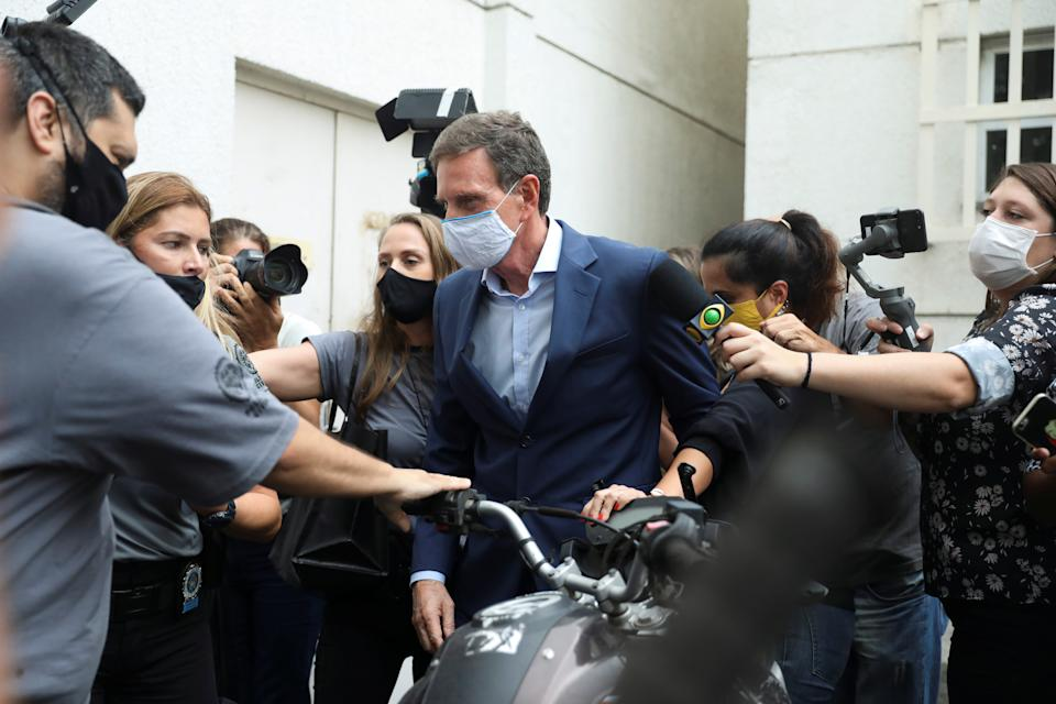 Rio de Janeiro's Mayor Marcelo Crivella is escorted by police officers after being detained, at the police headquarters in Rio de Janeiro, Brazil, December 22, 2020.  REUTERS/Pilar Olivares