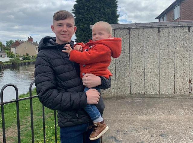 Rylan Ferguson, 15, holding little Reggie after saving him from drowning in a canal. (SWNS)