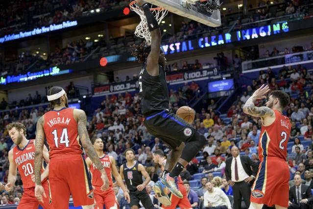 Los Angeles Clippers forward Montrezl Harrell (5) dunks against New Orleans Pelicans guard Lonzo Ball (2) in the first half an NBA basketball game in New Orleans, Saturday, Jan. 18, 2020. (AP Photo/Matthew Hinton)