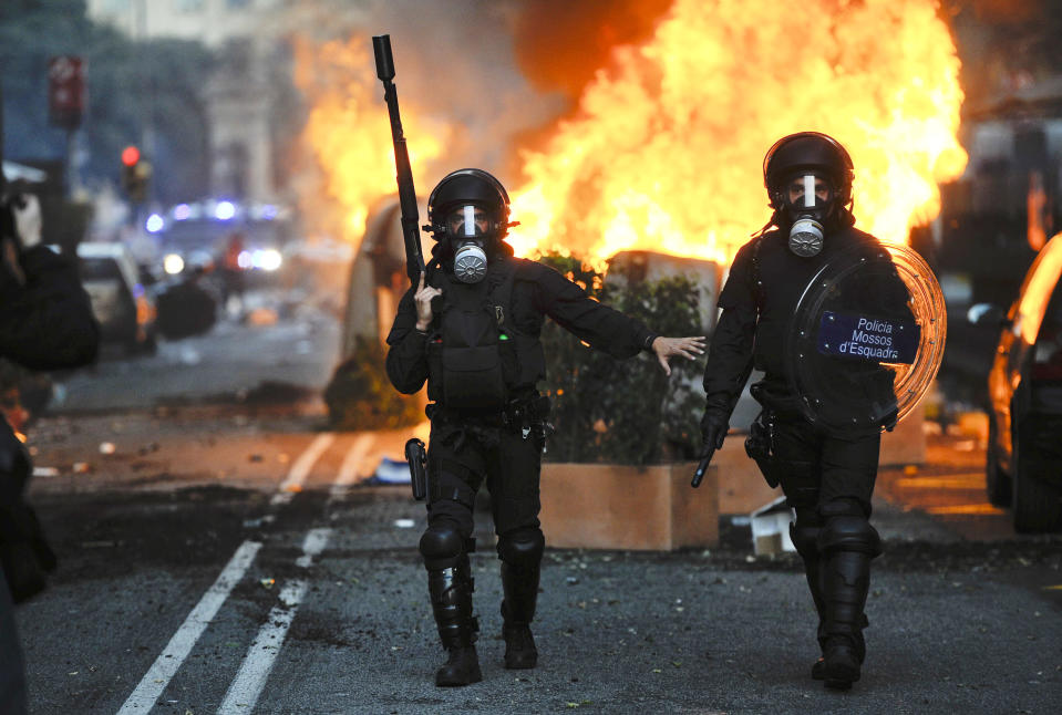 Riot police walk past burning garbage containers during heavy clashes with demonstrators during a 24-hour strike on March 29, 2012 in Barcelona, Spain. (Photo by David Ramos/Getty Images)