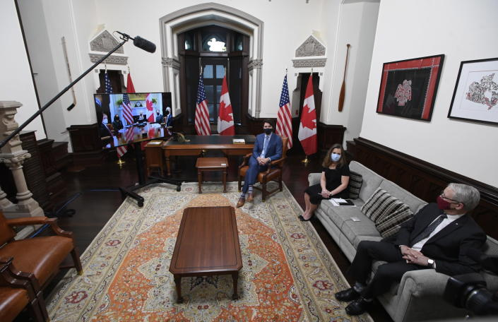 Canadian Prime Minister Justin Trudeau, Deputy Prime Minister and Minister of Finance Chrystia Freeland, and Foreign Affairs Minister Marc Garneau watch television as they meet virtually with United States President Joe Biden from his office on Parliament Hill in Ottawa, Ontario, Tuesday, Feb. 23, 2021. (Adrian Wyld/The Canadian Press via AP)