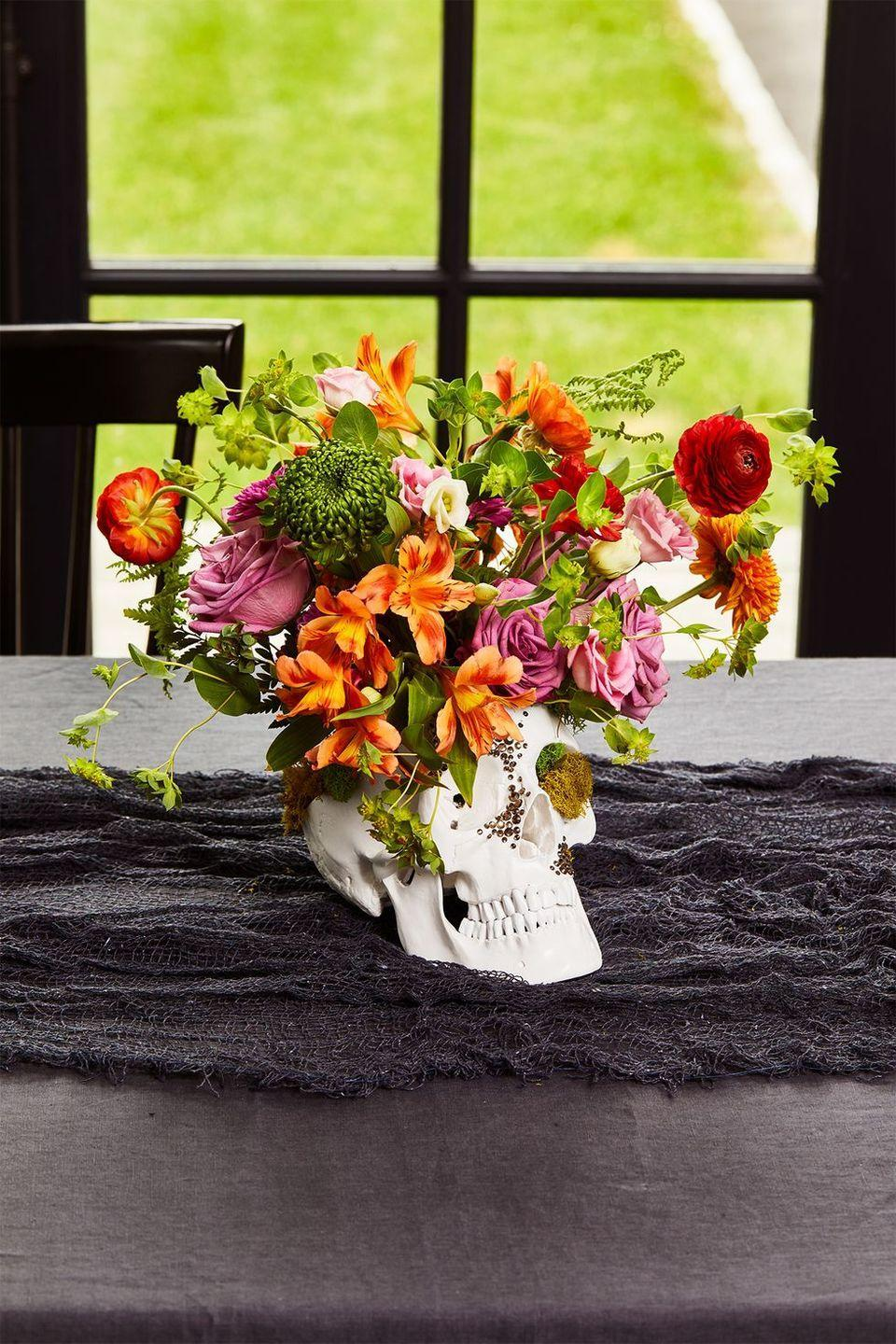 """<p>Give your Halloween table an otherworldly touch that would make Morticia Addams proud. Put a cup inside of a faux skull (make sure it has a removable top), then use tape to create a grid on its rim. This will help your flowers and greenery to stay put. Fill ⅔ with water and place your large flowers and greenery in the grid. Complete the arrangement by adding your delicate flowers. To help your floral centerpiece last longer, be sure to remove any leaves or extra stems that sit below the water line.</p><p><a class=""""link rapid-noclick-resp"""" href=""""https://www.amazon.com/gp/product/B00RLTKCPQ?tag=syn-yahoo-20&ascsubtag=%5Bartid%7C10055.g.421%5Bsrc%7Cyahoo-us"""" rel=""""nofollow noopener"""" target=""""_blank"""" data-ylk=""""slk:SHOP FAUX SKULL"""">SHOP FAUX SKULL</a></p>"""