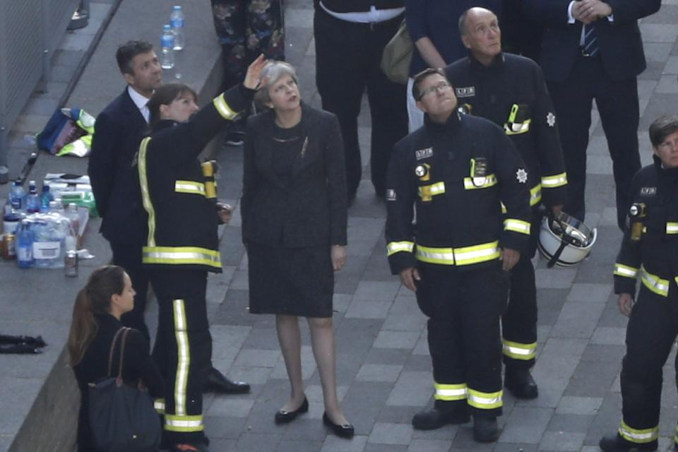 TOPSHOT - British Prime Minister Theresa May (C) speaks with Dany Cotton (L), London Fire Brigade commissioner as she visits the remains of Grenfell Tower, a residential tower block in west London which was gutted by fire on June 15, 2017. Firefighters searched for bodies today in a London tower block gutted by a blaze that has already left 12 dead, as questions grew over whether a recent refurbishment contributed to the fire. / AFP PHOTO / Tolga AKMEN        (Photo credit should read TOLGA AKMEN/AFP via Getty Images)