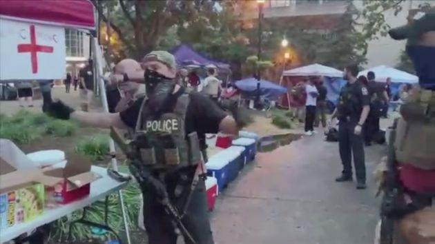 A police officer, wearing a tactical vest, gestures for people to step back after the shooting.
