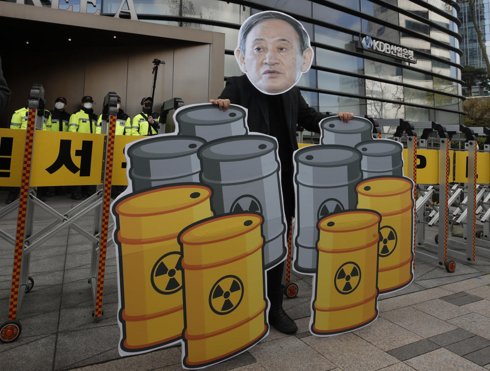 A member of youth groups wearing a cutout of Japanese Prime Minister Yoshihide Suga performs to denounce his government's decision, in Seoul, South Korea, Tuesday, April 13, 2021. Japan's government decided Tuesday to start releasing massive amounts of treated radioactive water from the wrecked Fukushima nuclear plant into the Pacific Ocean in two years - an option fiercely opposed by local fishermen and residents. (AP Photo/Lee Jin-man)