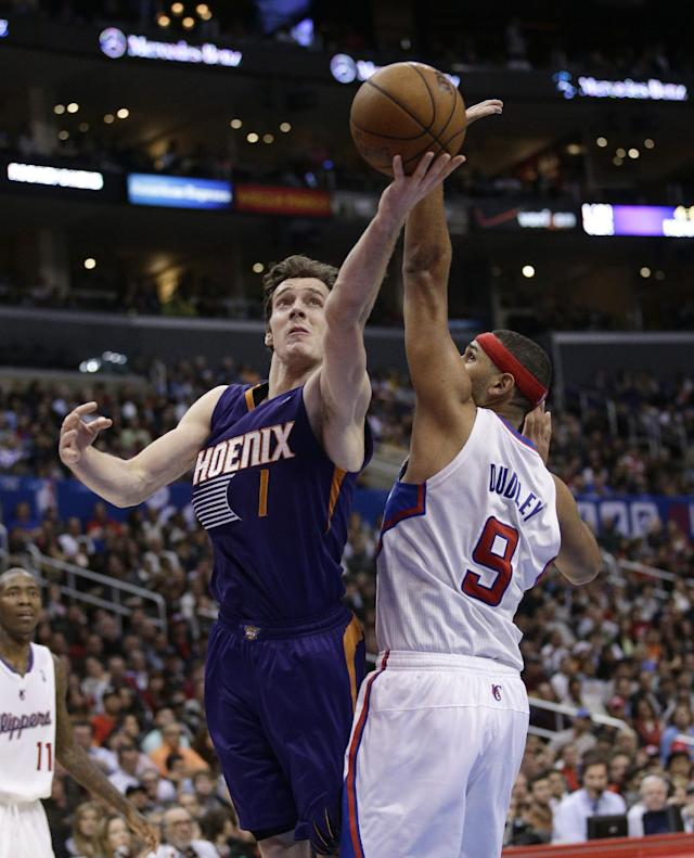 Phoenix Suns' Goran Dragic, left, of Slovenian, puts up a shot against Los Angeles Clippers' Jared Dudley during the second half of an NBA basketball game on Monday, Dec. 30, 2013, in Los Angeles. (AP Photo/Jae C. Hong)